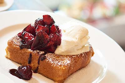 French toast covered with berries, whipped cream and powdered sugar