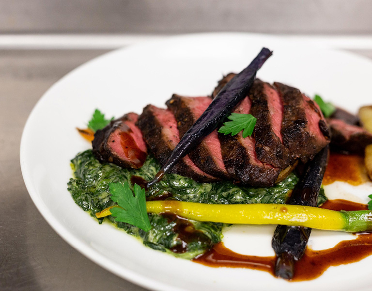 Hanger steak over creamed spinach