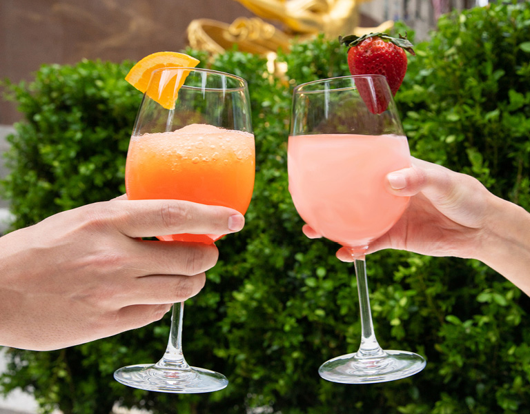 Frosé with a fresh strawberry and frozen aperol spritz
