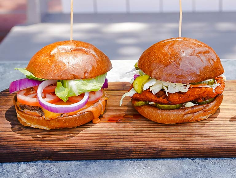 Two burgers on a wooden tray