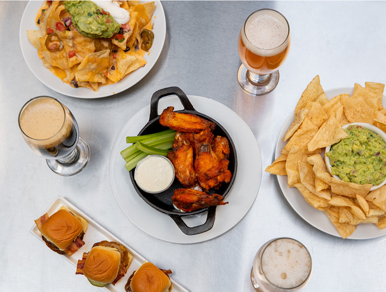 Chicken wings, chips and guacamole, loaded nachos and beer served at The Beer Bar in NYC