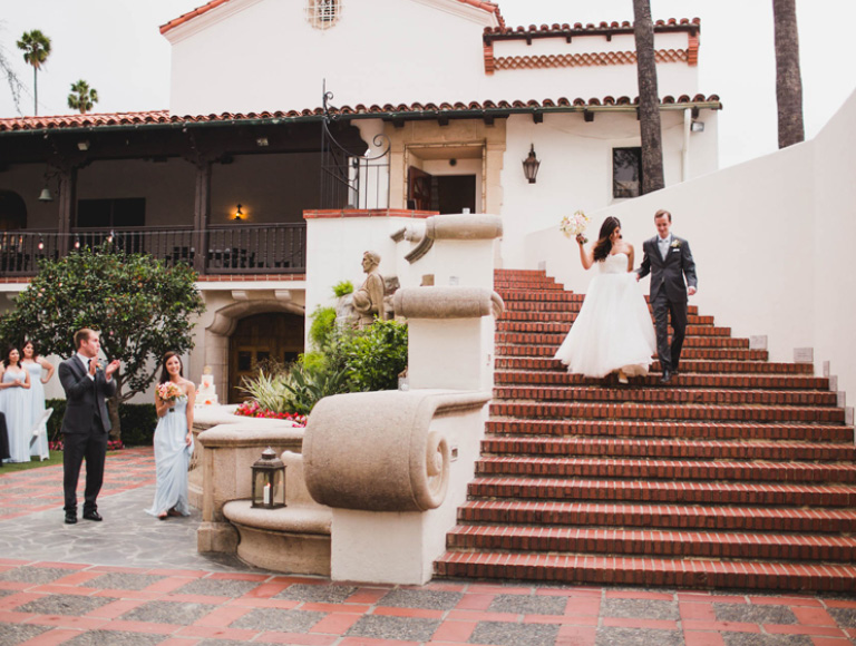 Newlyweds walking down grand brick staircase to the outdoor reception area