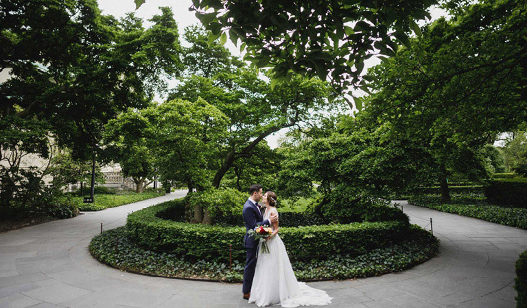 A bride and groom embrace outside at Brooklyn Botanic Garden