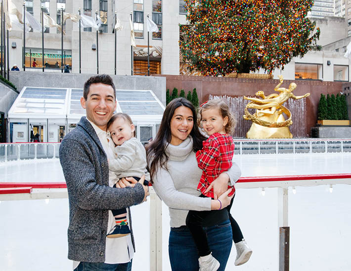 Family with young children stand near The Rink at Rockefeller Center